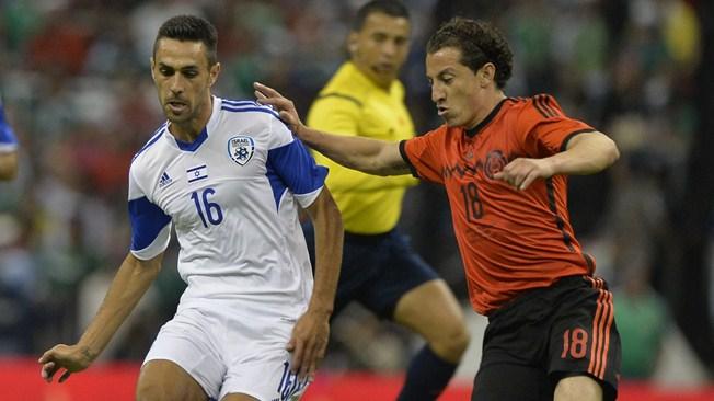 Mexico's foward Andres Guardado (R) disputes the ball with Israel's Eran Zahavi