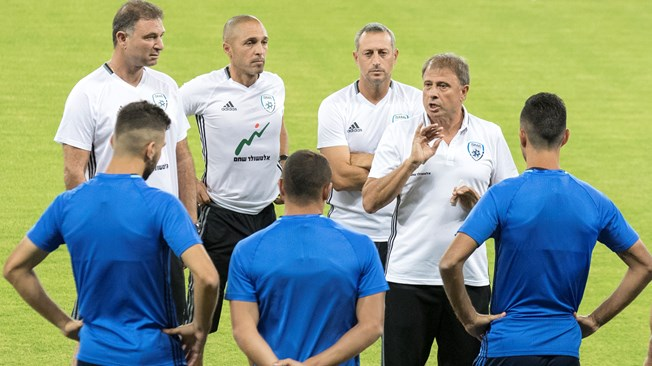 Israeli national football team's head coach, Elisha Levy (3rdR) talks to his players